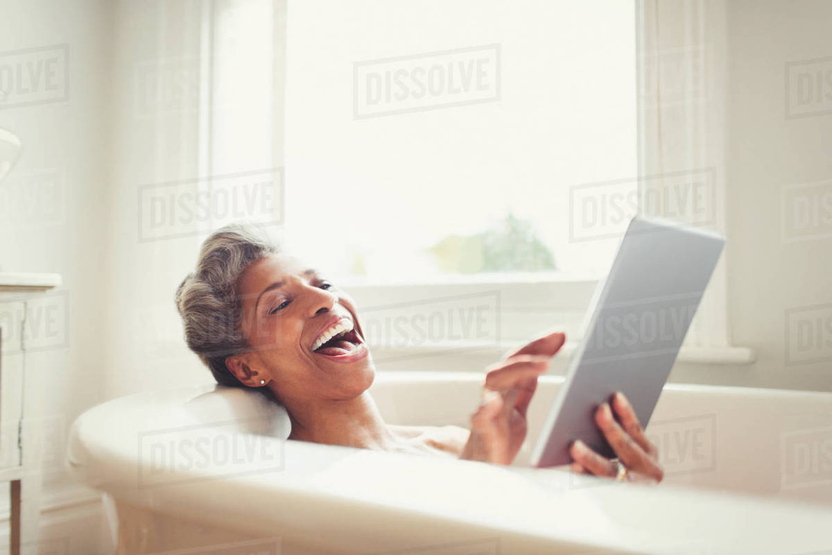 Laughing mature woman using digital tablet in bathtub Royalty-free stock photo