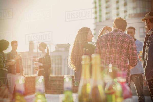 Young adult friends socializing at sunny rooftop party Royalty-free stock photo