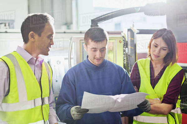 Workers reviewing paperwork in steel factory Royalty-free stock photo