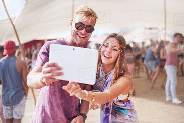 Young couple taking selfie with digital tablet at music festival Royalty-free stock photo