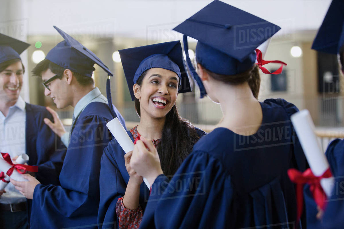 Happy female college student graduates with cap and gown and ...