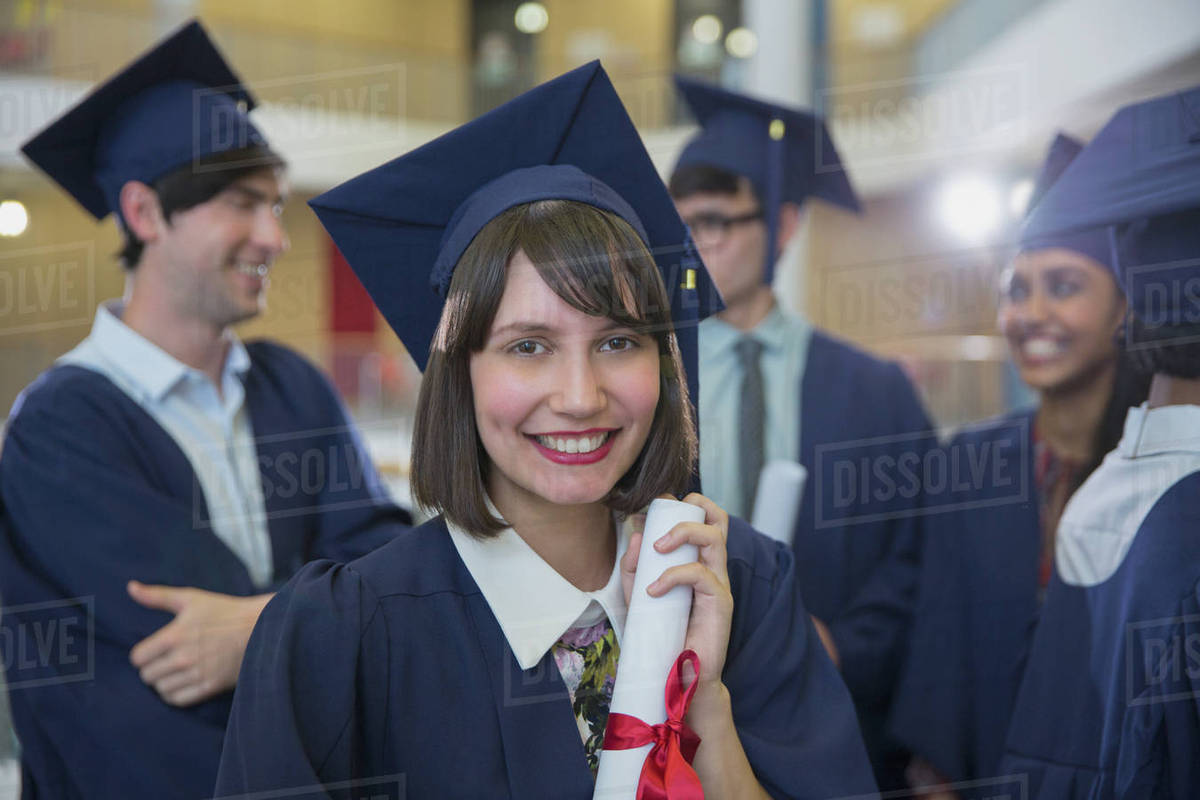 Portrait smiling female college graduate in cap and gown holding ...