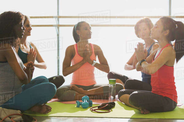 Serene women meditating in yoga class gym studio Royalty-free stock photo