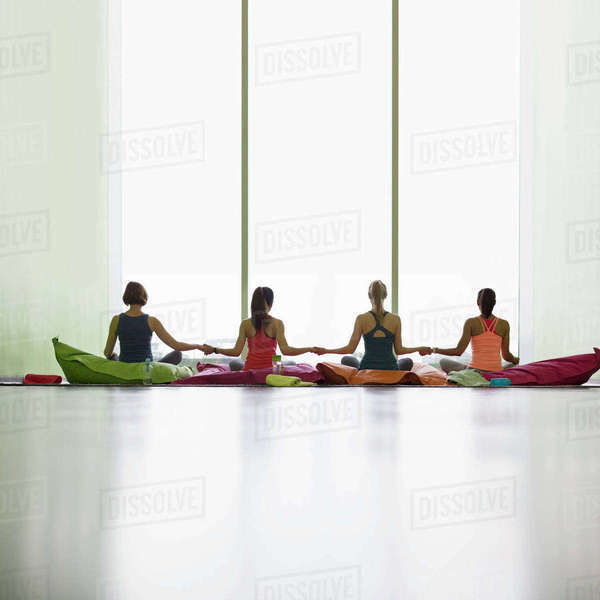 Women on cushions holding hands at window in restorative yoga gym studio Royalty-free stock photo