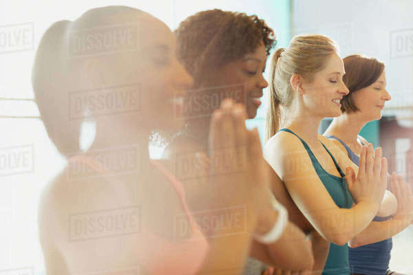 Serene women practicing yoga with hands at heart center in gym studio Royalty-free stock photo