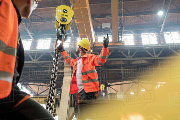 Steel workers fastening chain to crane in factory Royalty-free stock photo
