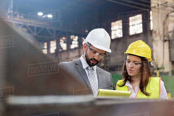 Manager and female steel worker meeting in factory Royalty-free stock photo