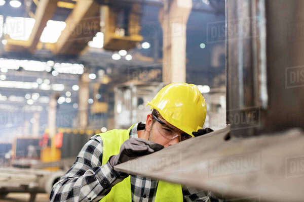 Steel worker examining steel in factory Royalty-free stock photo