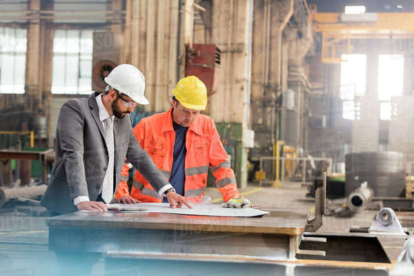 Manager and steel worker engineer reviewing blueprints in factory Royalty-free stock photo