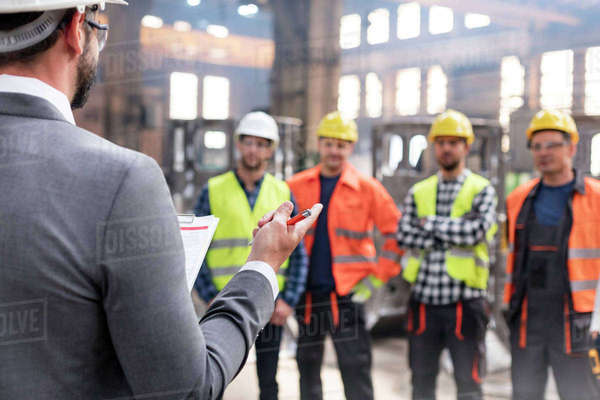Steel workers listening to manager in meeting in factory Royalty-free stock photo