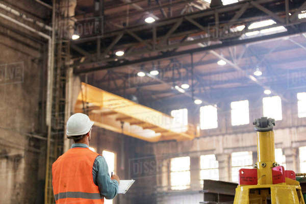 Steel worker with clipboard looking up in factory Royalty-free stock photo