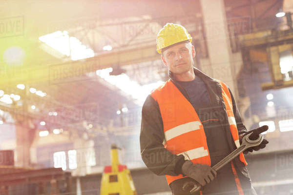 Portrait confident steel worker holding large wrench in factory Royalty-free stock photo