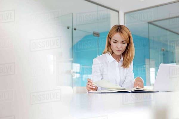 Focused businesswoman reviewing paperwork at laptop in conference room Royalty-free stock photo