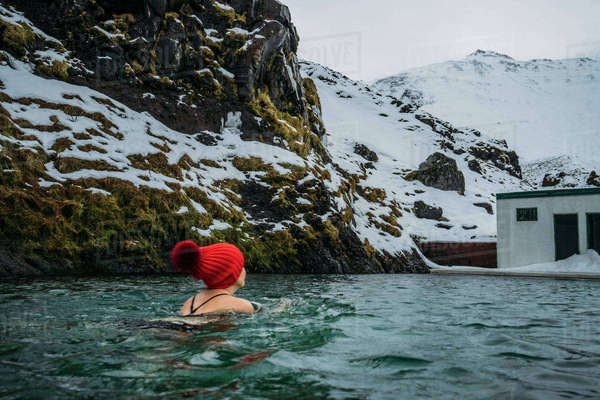 Woman in stocking cap swimming below snowy mountains, Iceland Royalty-free stock photo
