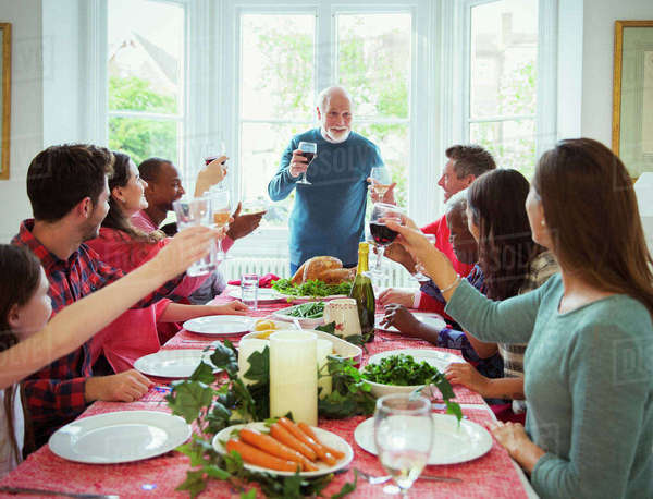 Grandfather making toast with wine at Christmas dinner table Royalty-free stock photo
