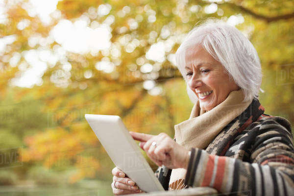 Older woman using tablet computer in park Royalty-free stock photo