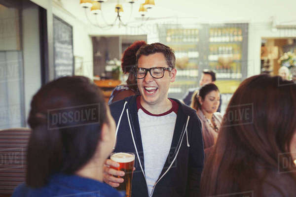 Man laughing and drinking beer with friends at bar Royalty-free stock photo