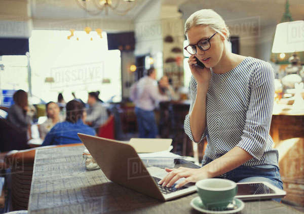 Creative businesswoman talking on cell phone and using laptop in cafe Royalty-free stock photo
