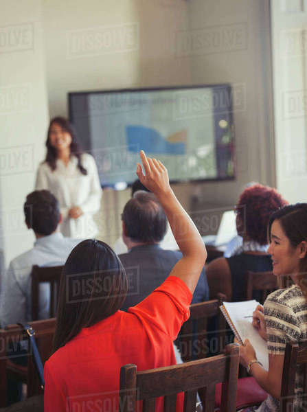 Businesswoman in audience asking question at business conference Royalty-free stock photo