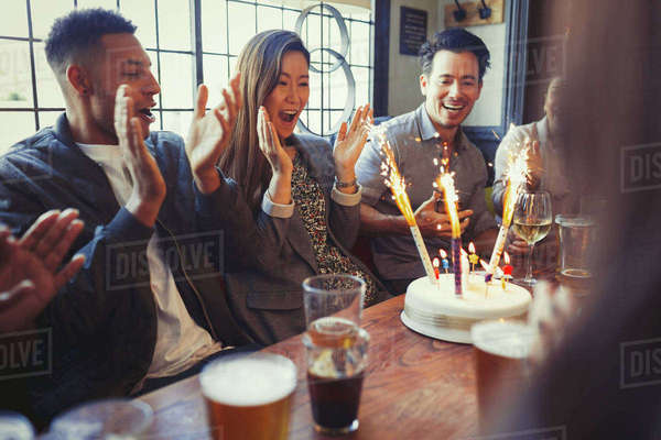 Friends cheering for woman celebrating birthday with fireworks cake at table in bar Royalty-free stock photo