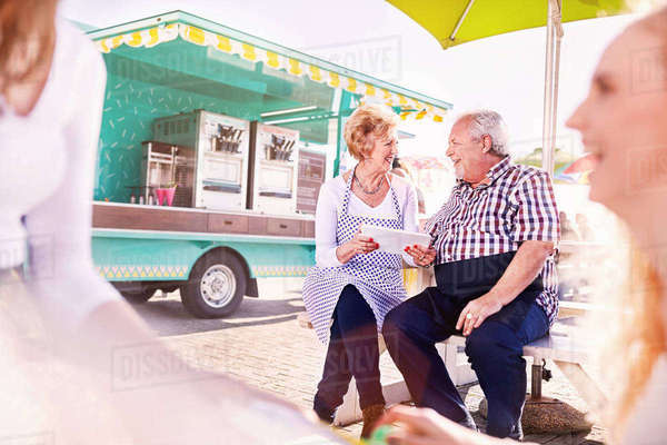 Smiling senior business owners using digital tablet outside food cart Royalty-free stock photo