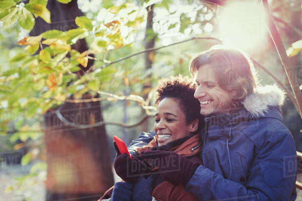 Smiling couple using cell phone in sunny autumn park Royalty-free stock photo