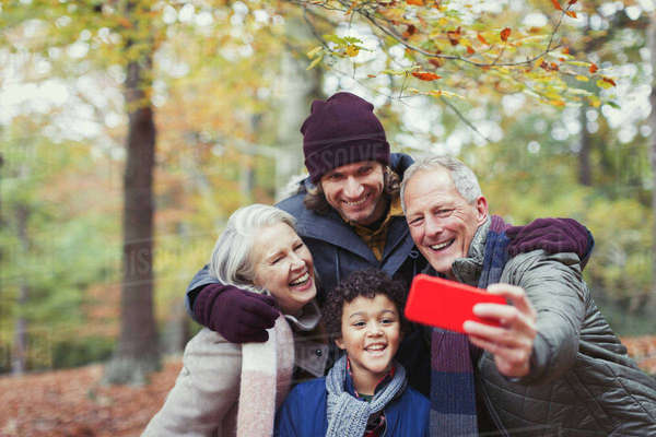 Multi-generation family taking selfie with camera phone in autumn woods Royalty-free stock photo