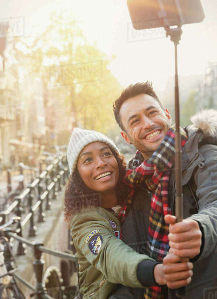 Smiling young couple taking selfie with selfie stick on urban street Royalty-free stock photo