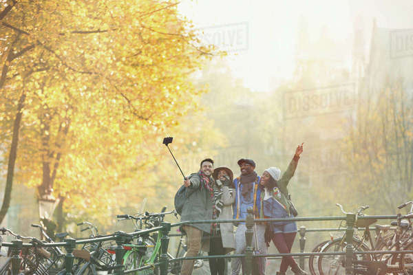 Playful young friends taking selfie with selfie stick on urban autumn bridge, Amsterdam Royalty-free stock photo
