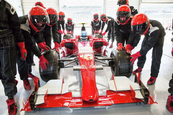 Pit crew pushing formula one race car into repair garage Royalty-free stock photo