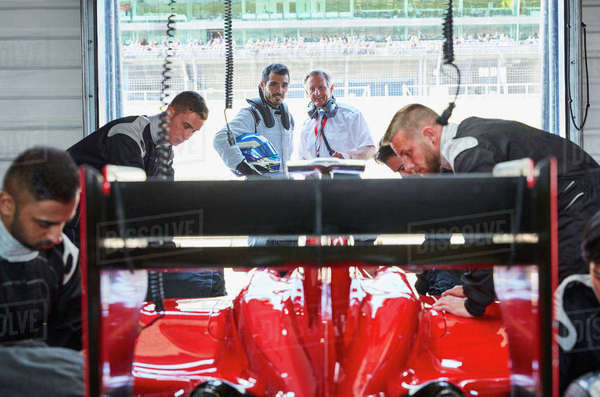 Pit crew working on formula one race car in repair garage Royalty-free stock photo