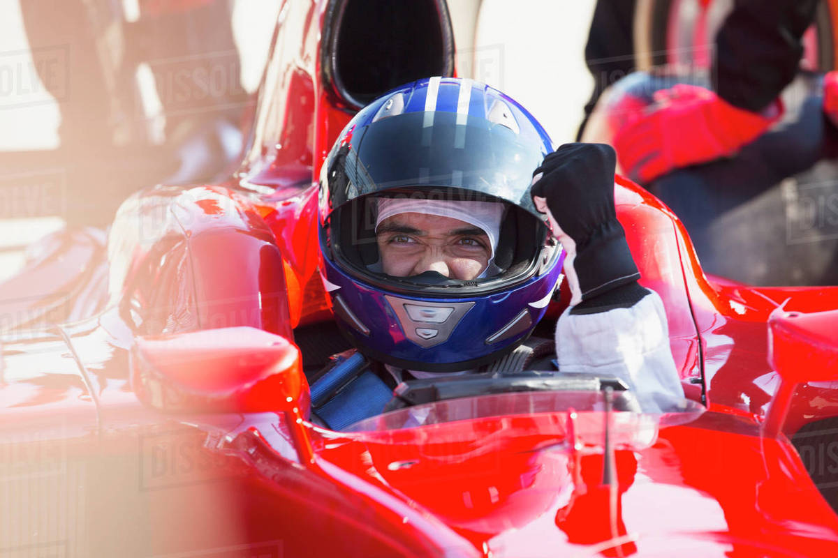 Formula one race car driver in helmet gesturing, celebrating victory Royalty-free stock photo