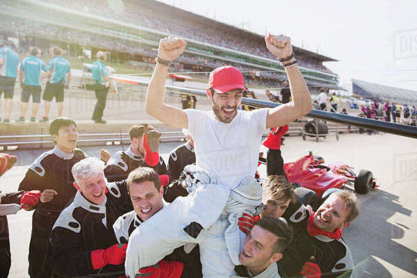 Formula one racing team carrying driver on shoulders, celebrating victory on sports track Royalty-free stock photo