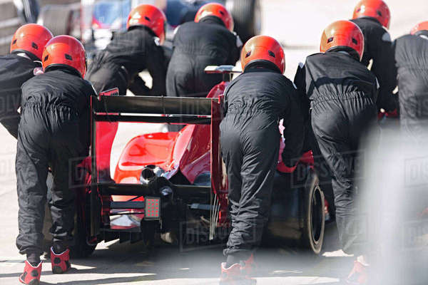 Pit crew pushing formula one race car out of pit lane Royalty-free stock photo