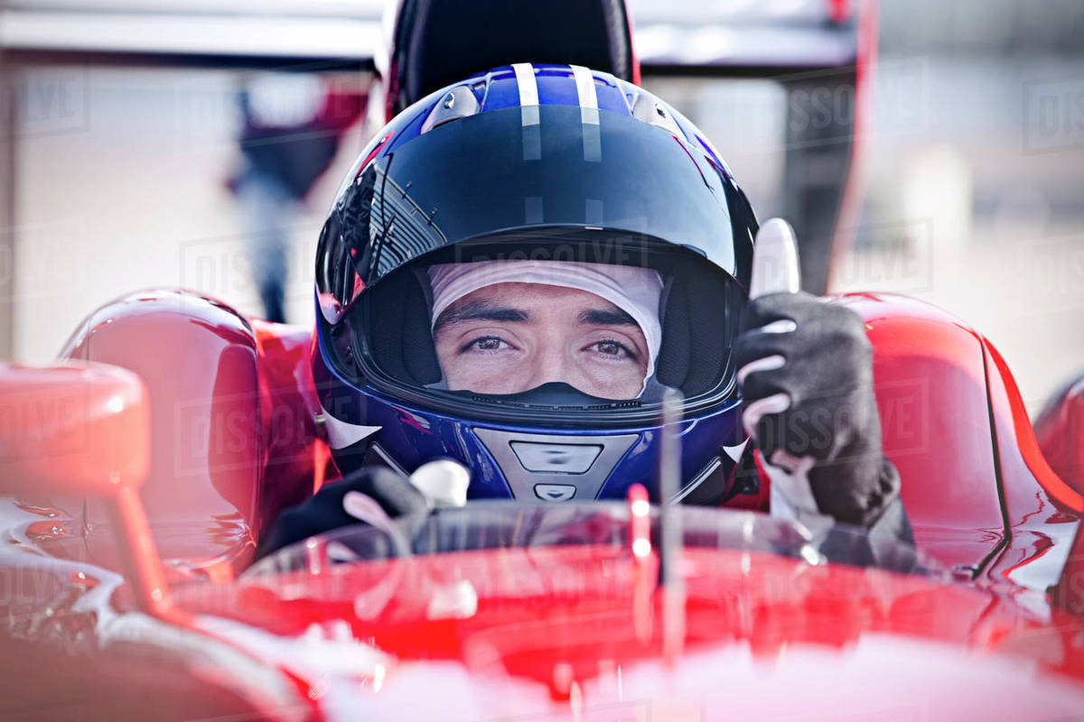Portrait confident male formula one race car driver gesturing thumbs-up Royalty-free stock photo
