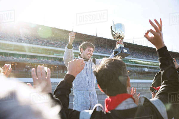 Formula one racing team cheering for driver with trophy, celebrating victory on sports track Royalty-free stock photo