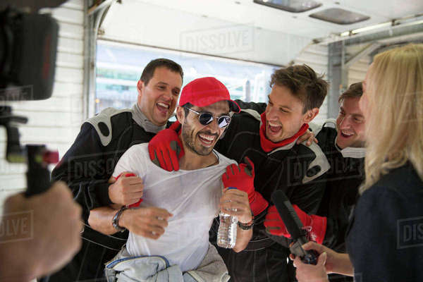 Formula one driver and team celebrating victory in repair garage Royalty-free stock photo