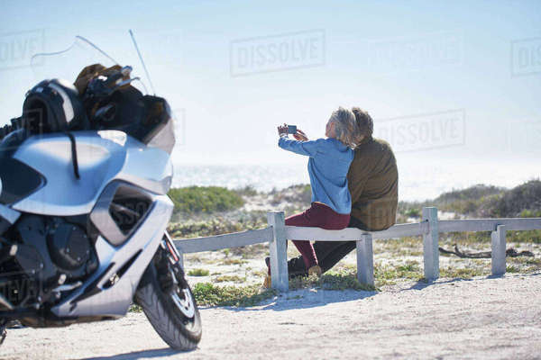 Senior couple taking selfie at sunny roadside near motorcycle Royalty-free stock photo