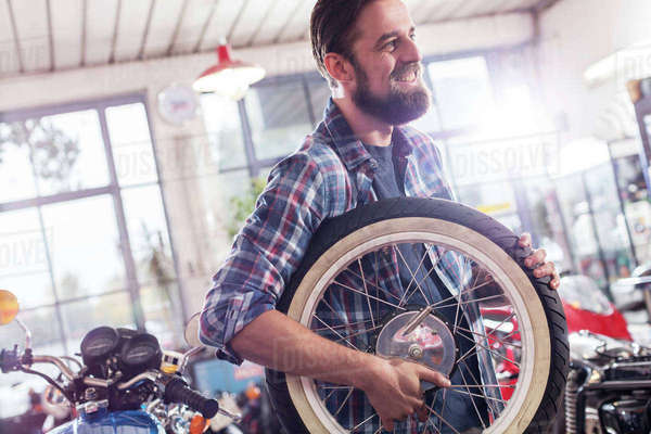 Smiling motorcycle mechanic carrying wheel in shop Royalty-free stock photo