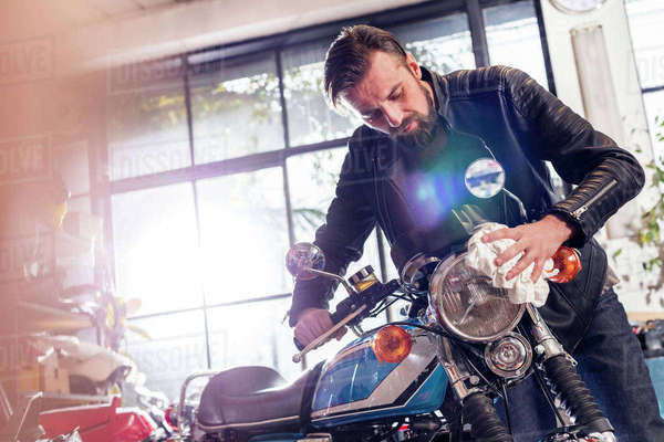 Male motorcycle mechanic wiping motorcycle in workshop Royalty-free stock photo