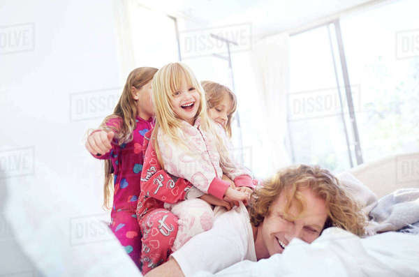 Playful daughters laying on top of father on bed Royalty-free stock photo