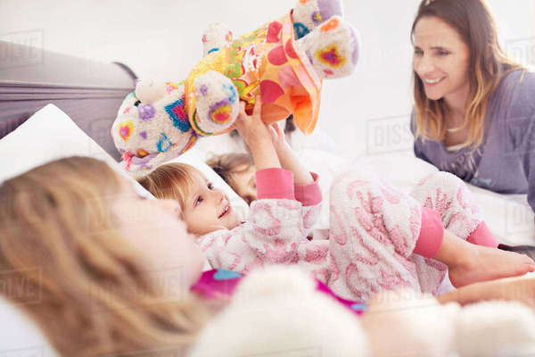 Mother watching daughter playing with stuffed animal on bed Royalty-free stock photo
