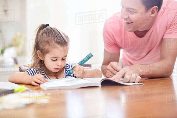 Father watching daughter coloring with crayon and coloring book at table Royalty-free stock photo