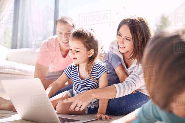 Family using laptop in sunny living room Royalty-free stock photo