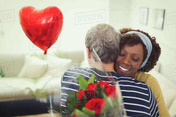 Wife hugging husband giving Valentine's Day balloon and rose bouquet Royalty-free stock photo