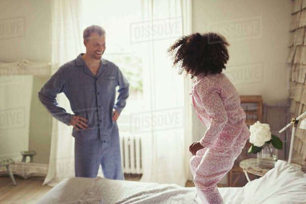 Multi-ethnic father in pajamas watching daughter jumping on bed Royalty-free stock photo