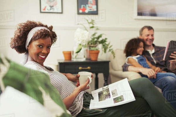 Portrait smiling woman relaxing with tea and magazine on sofa Royalty-free stock photo