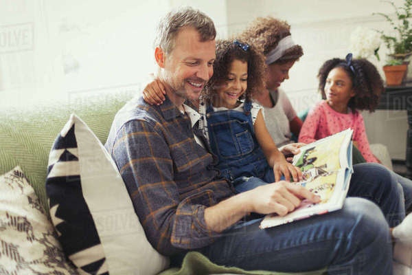 Smiling multi-ethnic father reading book with daughter on sofa Royalty-free stock photo