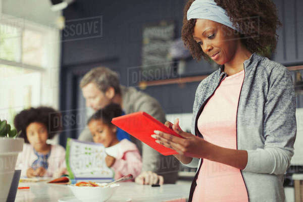Mother using digital tablet in kitchen near young family Royalty-free stock photo