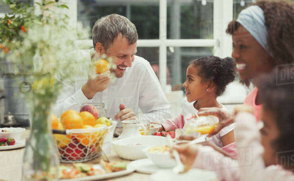 Multi-ethnic father and daughter eating breakfast at table Royalty-free stock photo
